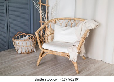 wicker wooden chair with white pillows and a blanket