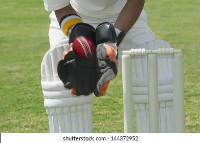 Wicket keeper standing behind stumps and catching a ball
