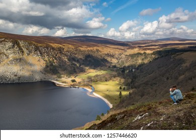 WICKLOW, IRELAND - APRIL 23, 2016: Panoramic landscape view of a man in the foreground sitting high up looking over a lake and mountain in the Wicklow Mountains in Ireland April 23, 2016.