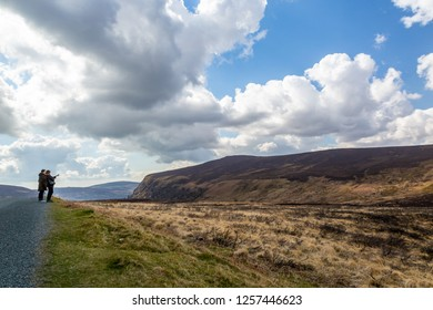 WICKLOW, IRELAND - APRIL 23, 2016: Panoramic landscape view of two woman in the foreground looking at mountains and sky in the Wicklow Mountains in Ireland April 23, 2016.