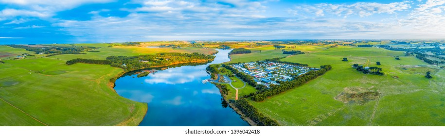 Wide aerial panorama of Hopkins River, Holiday Park and surrounding agricultural land in Warrnambool, Australia
