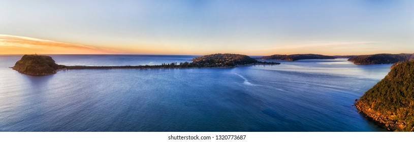 WIde aerial panorama over Broken Bay where Hawkesbury river enters Pacific ocean with distant Barrenjoye head and lighthouse connected to the land by narrow stripe of Palm beach.