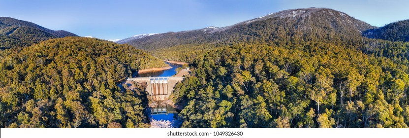 Wide aerial panorama over Guthega dam in Snowy mountains on Snowy river during winter season with distant mountain peaks covered by snow.