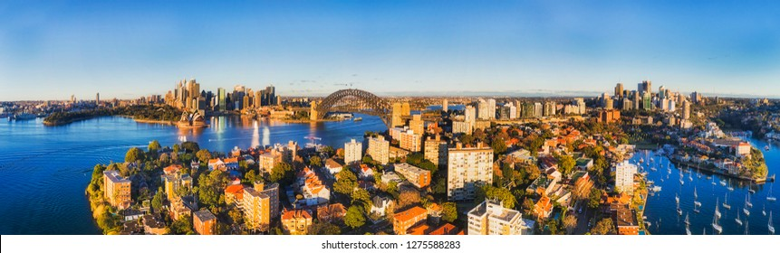 Wide aerial panorama over rooftops of residential buildings in Kirribilli suburb of Sydney with view from city CBD landmarks on harbour shores to North Sydney CBD.