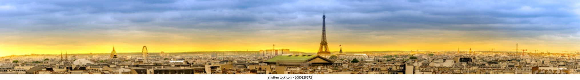 Wide aerial panorama of Paris skyline at sunset with view of most of landmarks, Eiffel tower, Invalides, Pantheon, Ferris wheel, Madeleine, Grand Palais, Notre Dame, Sainte-Chapelle, Petit Palais