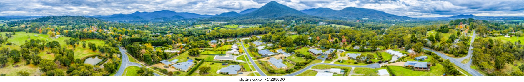Wide aerial panorama of scenic countryside with houses surrounded by forest and mountains. Healesville, Victoria, Australia - Shutterstock ID 1422880100