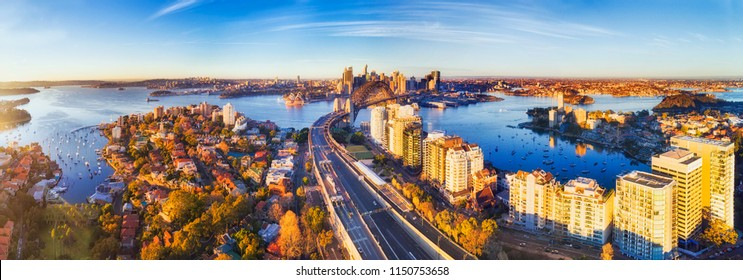 Wide aerial panorama of Sydney city CBD landmark around Harbour viewed from North Sydney along Warringah freeway lit by warm morning light.