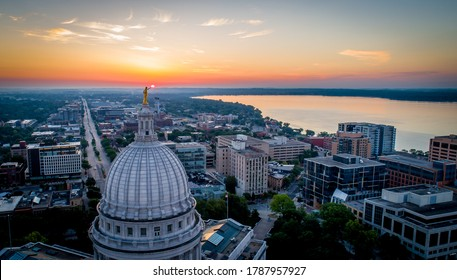 Wide aerial shot of a dramatic, fiery sunrise over the Wisconsin State Capitol. Statue atop the dome appears to hold the rising sun.
