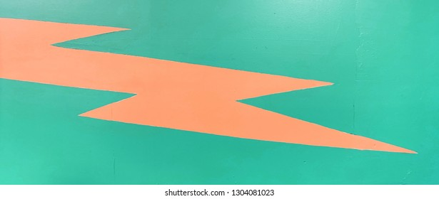 Wide anamorphic shot of retro 90's pop art lightning strike bolt painted on walls of bowling alley.