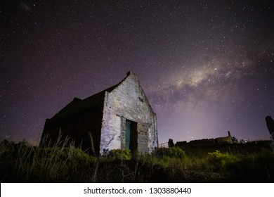 Wide angle astrophotography scene of an old abandoned building with the bright nigh sky above it.