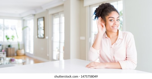 Wide angle of beautiful african american woman with afro hair smiling with hand over ear listening an hearing to rumor or gossip. Deafness concept.