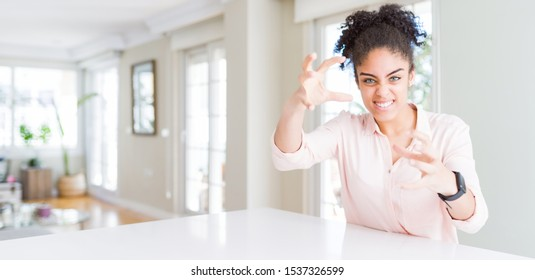 Wide angle of beautiful african american woman with afro hair Shouting frustrated with rage, hands trying to strangle, yelling mad