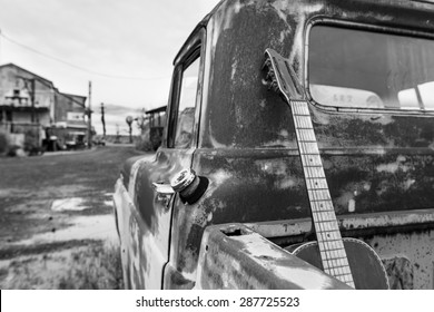Wide angle black and white shot of an old acoustic guitar in the bed of an old rusted out truck parked in the dirt in Clarksdale Mississippi