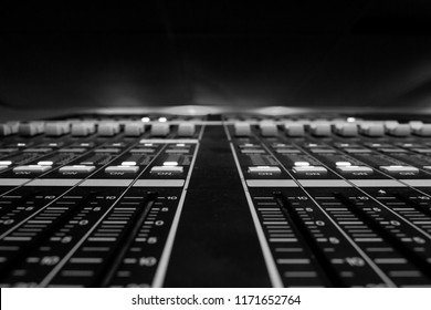 Wide angle closeup of Pro Audio Digital Mixing Console. White Faders and black control Console