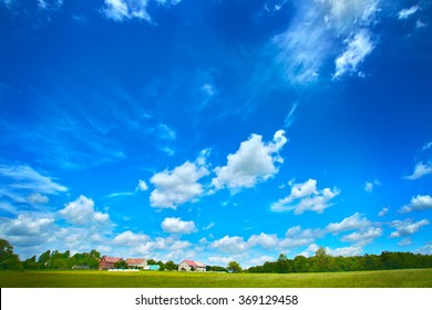 Wide angle clouds over green meadow with hoses on a farm under blue sky