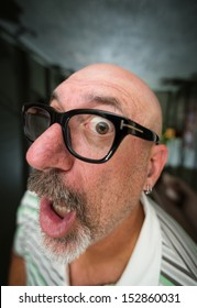Wide angle color shot of a middle aged bald man with black glasses and a goatee looking with one eye into camera lens