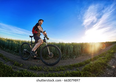 Wide angle of the cyclist standing on the trail on the field against beautiful landscape.