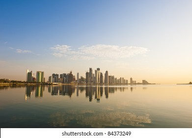 Wide angle of Doha, Qatar, where the skyline changed drastically over the past 5 years. Image captured early in the morning with the sun rising from the right and some rare fluffy clouds in the sky..