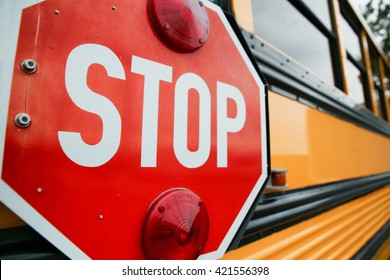 wide angle front view of a bright yellow orange school bus and the big red stop sign