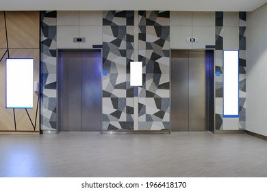 Wide angle front view of modern lift lobby, with blank advertising media spaces for mockup purpose. For OOH concept in office or retail environment