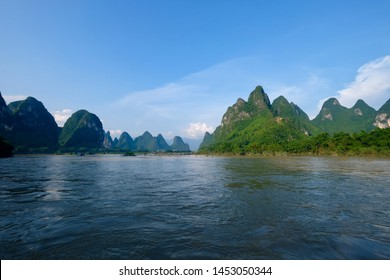 Wide angle of green mountains above blue water. Sunny blue sky white clouds. At the Lijiang ( Li river) in Yangshuo Guilin city China. Karst landform