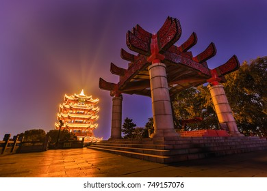 """Wide angle HDR (high dynamic range) shot of bell tower against the illuminated Yellow Crane Tower at night in Wuhan, Hubei, China, 4 Chinese letters on tower is """"Mu Ji Tian Chu"""" means """"amazing heaven"""""""