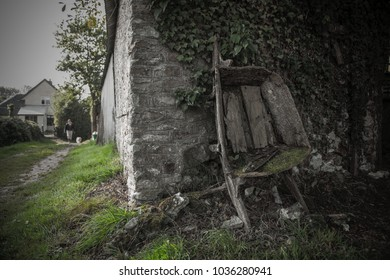 Wide angle image of an old wheelbarrow leaning on a farm building in Devon, UK