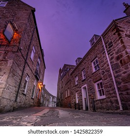 A wide angle image of the stone cobbled streets and granite houses of Hugh Town, St Marys, Isles of Scilly, Cornwall, taken at dusk.
