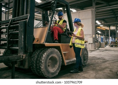 Wide angle image of workers in factory. Woman with tablet talking to forklift driver