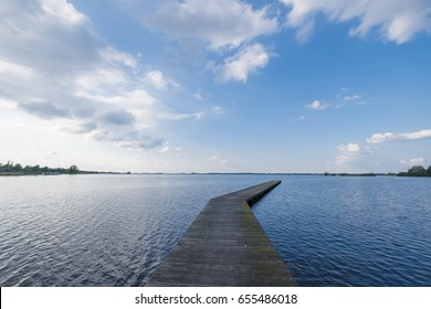 Wide angle of a jetty with very calm water and blue cloudy sky