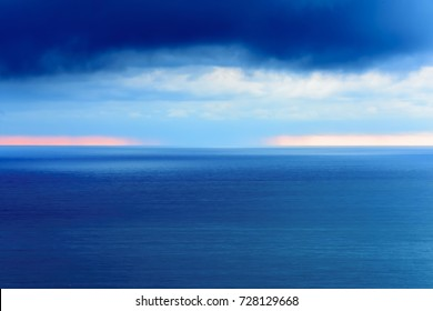 Wide angle long exposure panorama landscape seascape vista with shades of green, aqua, turquoise and blue under blue skies with low lying puffy clouds.