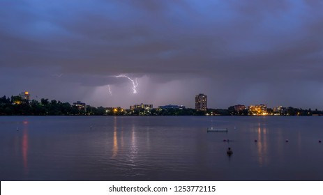 A Wide Angle Long Exposure Shot of a Lightning Bolt over Lake Bde Maka Ska in Minneapolis as a Swimmer Watches during a Summer Twilight