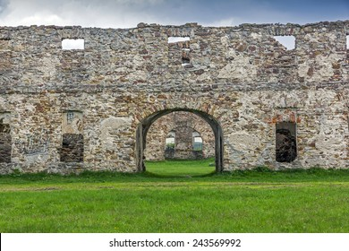 Wide angle old ruins built with stone bricks and overgrown with plants, with a gate with an arc in the center and numerous window holes giving view across the ruins