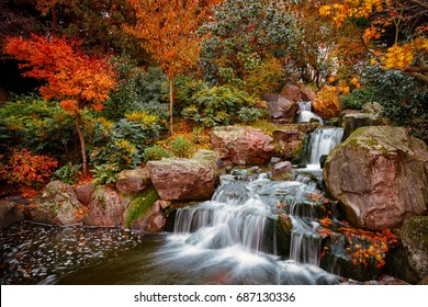 A wide angle panning shot showing exquisite details of lush Japanese gardens including a waterfall during early autumn