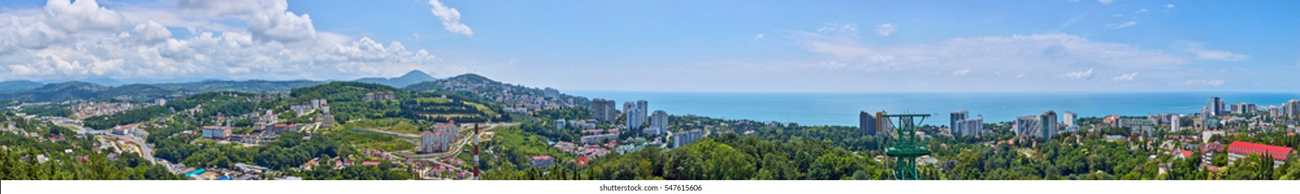Wide angle panorama of blue coast of Black Sea in Sochi with houses under summer cloudy sky