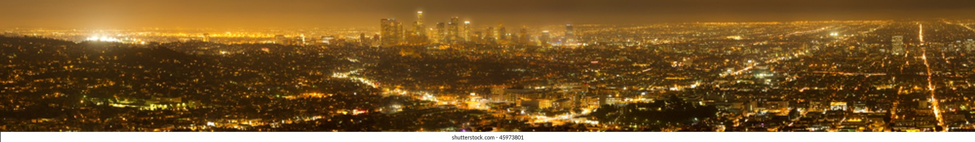 Wide angle panorama image of Los Angeles skyline and city at night.