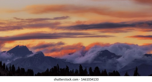 Wide angle panorama silhouette forest and mountain tops in red orange blue clouds gradient sunset