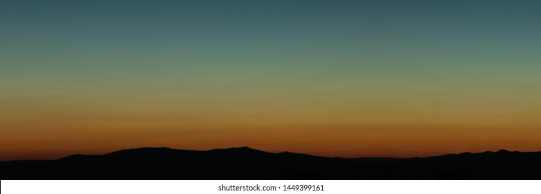 Wide angle panorama silhouette mountain tops in orange blue gradient sunset