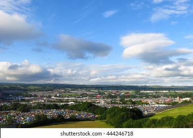 Wide angle panoramic view of Glastonbury Festival beneath sunny blue sky taken from a hillside. This arts and music event is the largest greenfield festival in the world.