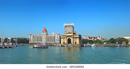 Wide angle panoramic view of Mumbai's famous heritage landmark Gateway of India as seen from the Arabian sea and busy sea front with colorful excursion ferry boats in foreground. Copy space.