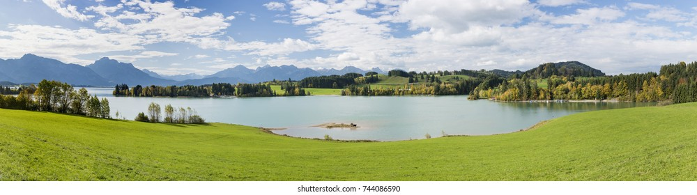 wide angle panoramic view to rural landscape in Bavaria with alps mountains and lake Forggensee