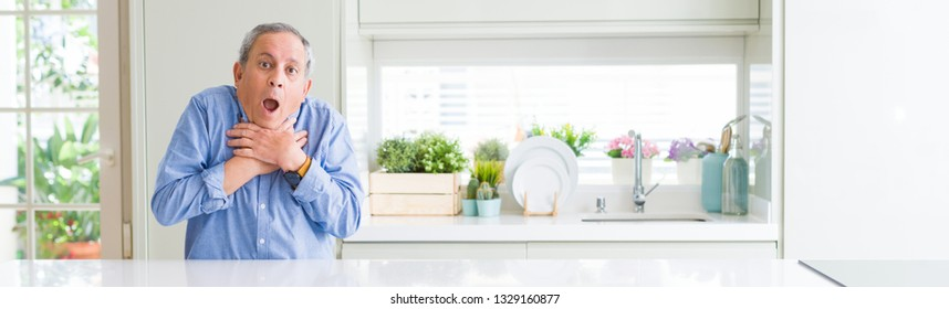 Wide angle perspective of handsome senior man at home shouting and suffocate because painful strangle. Health problem. Asphyxiate and suicide concept.