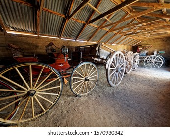 Wide angle photo inside old Barn with horse drawn vehicles of Carts and Buggy's.  Junee, Australia.