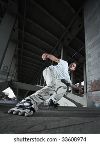 Wide angle photo of a rollerskater performing extreme braking (Power Slide element) in urban scenery