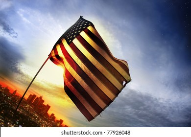 Wide angle photo of a tattered American flag blowing in the wind over a distant city lit by golden sunset light