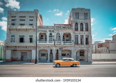 Wide angle photo a yellow old American car in the streets of Havana, Cuba with architectural background and summer blue skies. Wednesday, March 28, 2018
