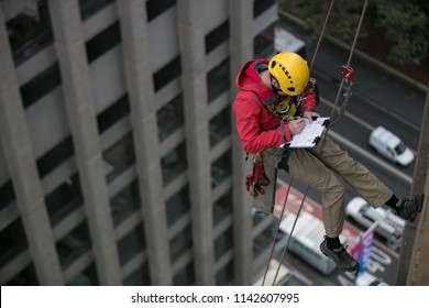 Wide angle pic of male rope access inspector worker working at height and abseiling down, hanging on rope in fall arrest position at high rise building written maintenance report,  Sydney, Australia