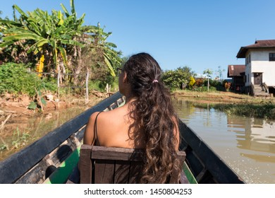 Wide angle picture of the back of long hair woman looking the beautiful nature during boat trip in Inle Lake, Myanmar