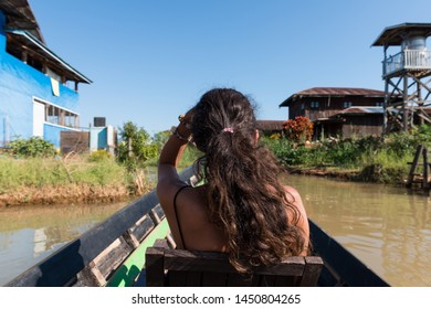 Wide angle picture of the back of long hair woman protecting her face from the sun during boat trip in Inle Lake, Myanmar