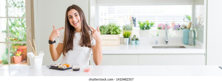 Wide angle picture of beautiful young woman eating asian sushi from delivery smiling confident showing and pointing with fingers teeth and mouth. Health concept.